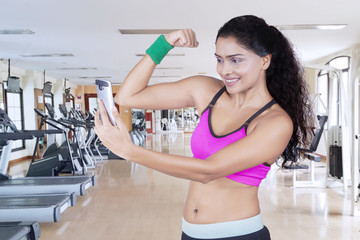 Indian woman taking photo her arm muscle