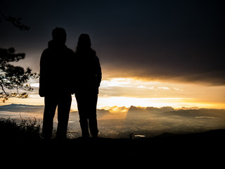silhouette couple standing on moutains with sunrise nature landscape background