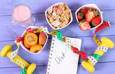Healthy food, dumbbells, tape measure and notebook for notes, slimming, healthy and sporty lifestyle