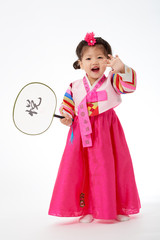 Smile Korean little girl wearing a Traditional Hanbok dress and holding a fan in white background. The characters on the dress means happiness and healthy. The character on the fan means happy.
