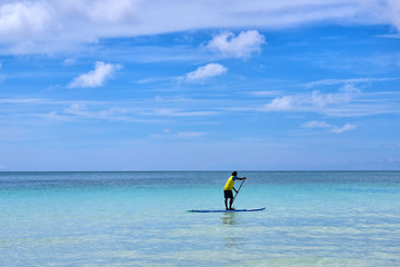 Man is enjoy a view in standup paddleboarding over the ocean