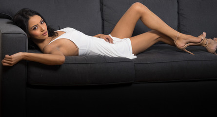 Beautiful sexy woman lying on couch