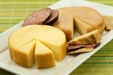 Cheese Wheels with Summer Sausage on Green