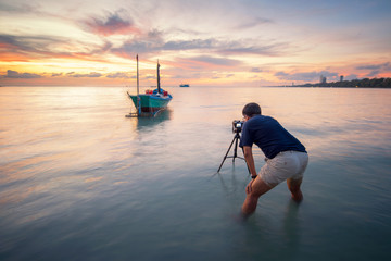 Photographer is taking a picture of sunrise with traditional fishing boats during sunset time at thailand