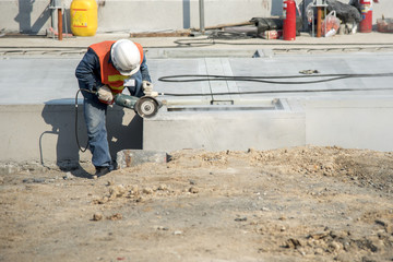 worker cutting concrete in construction site