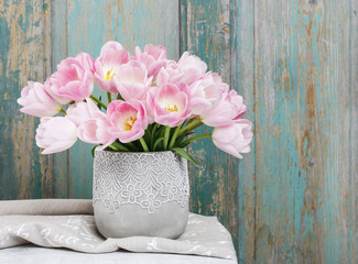 Bouquet of pink tulips, rustic wooden background.
