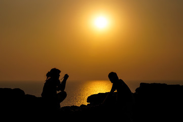 Silhouette of young woman take a picture of his boyfriend in the background of sunset at the sea
