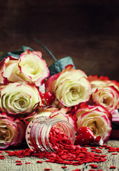 Red sweet heart, Valentines Day card on background of fresh pink and white roses, selective focus