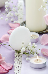 Easter table floral decoration with goose eggs, candles and gypsophila paniculata twigs