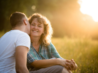 Young adult boy kissing her mother on cheek