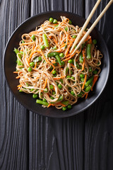 Japanese soba salad with vegetables and sesame close-up on the table. Vertical top view