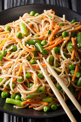 Buckwheat noodles with carrots, peas and chilli beans close-up on a plate. vertical, japanese style