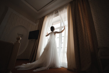 bride in a white dress with a plume opens the curtains