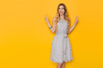 Smiling Young Woman In Summer Dotted Dress Is Showing Peace Sign