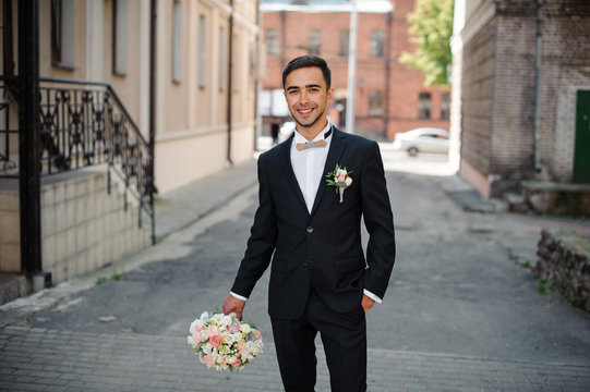 groom in a black suit walking down the street holding a pink bouquet