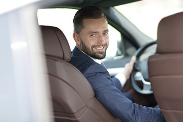 businessman sitting at the wheel of a car and looking at the camera