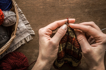 Mother's hands knitting a wool sock for a children. Balls in the basket on a brown rustic table. Womanly hobby for cold weather. Knitting concept.