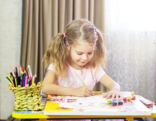 Девочка со светлыми волосами сидит за столом и рисует красками картину по номерам. Картина по номерам.