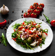 fresh salad with Green rucola, cheese, tuna, onion, pepper in white bowl on dark wooden background