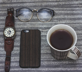 Toned image. Layout. Workplace freelancer. Smartphone, notebook, glasses, a cup of tea, clock,