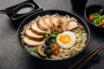 japanese ramen noodle with chicken, shiitake mushroms and egg in black bowl,