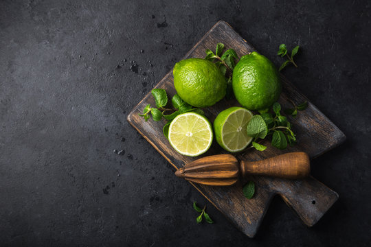 fresh green lime and mint on wooden cutting board
