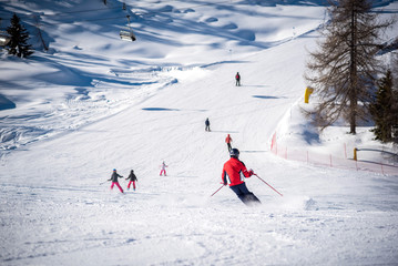 Skiers and ski track on a sunny day in the Alps