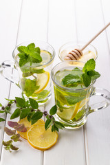 Two glass cups fresh mint tea with lemon and honey on white background.