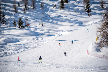 Skiers on a ski track on a beautiful sunny day in the Alps