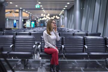 Young, beautiful girl talking on the phone in an empty airport terminal