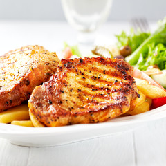 Grilled Pork Steaks with French Fries and Salad