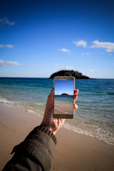 Young woman takes a picture of an island on a beach