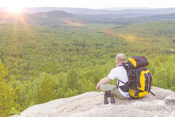 A tourist man is sitting with a backpack on top of a mountain, looking at the sunset. Camping, traveling, adventure.