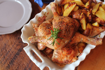Grilled chicken leg, quarter with potato for garnish. Top view. Wooden background