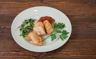 Roasted chicken breast fillet on a plate. Appetizing dish on the wooden brown table.