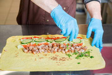 Cook prepares a shawarma. Ingredients on a big pita bread.