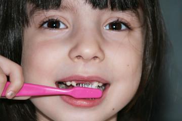 девочка утром в хорошем настроении чистит зубы , умывается и смеётся.