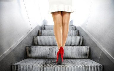 Slim woman legs with red sexy heels and stairs. Background of free space for your decoration.