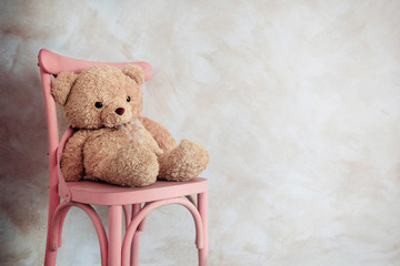 Sadness and Loneliness Concept. Lonely Teddy Bear Toy Siting Alone on Chair in House