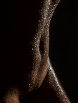 sexy nude female body with water drops on a black background