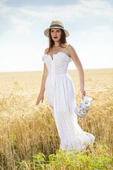 pretty girl from Europe has a romantic mood and walkes by wheat field in white dress