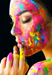 Beauty model girl with colorful paint on her face. Portrait of beautiful woman with flowing liquid paint isolated on black