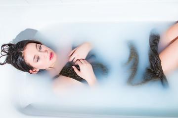Beautiful young model girl in dress in milk bath, relaxing, joy, rejuvenation, treatment