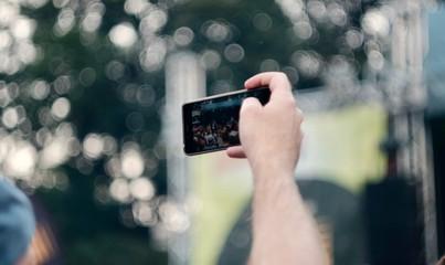 Mann fotografiert auf einem Konzert über eine Menschenmenge hinweg