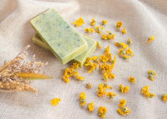 Homemade herbal chrysanthemum soap and dried chrysanthemum flower on brown sack background.