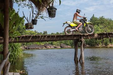 young man on cross motorbike crossing wooden bridge in jungle landscape -