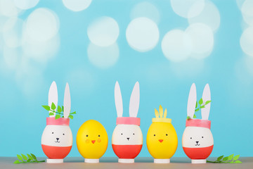 Easter holiday concept with cute handmade eggs: bunnies and chickens. young branches green behind the ears. blue background, beautiful bokeh and copy space