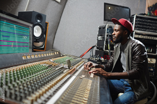 Young professional sitting by soundboard and mixing sounds while