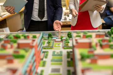 One of architect pointing at part of city layout during presentation of his project