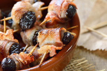 Leckere spanische Tapas: Getrocknete Pflaumen in Speck gerollt und gebraten – Delicious Spanish tapas:  Fried prunes wrapped in bacon